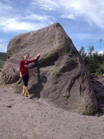 Standing in front of Alien Rock, shaped like a face and said to have flown to this location during a previous eruption