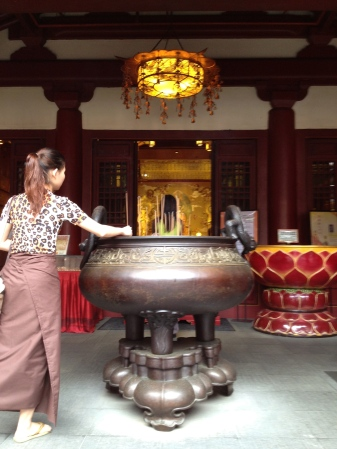A local offering a prayer at the entrance of Buddha Tooth Temple