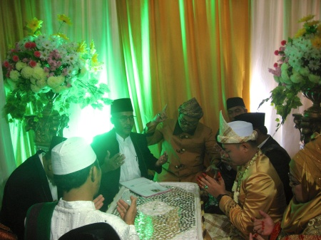 The Imam's prayer over the marital documents. The bride is still in the dressing room.